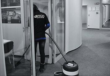 Sprzątanie biur poznań - Rygo, pracownik odkurzający w biurze